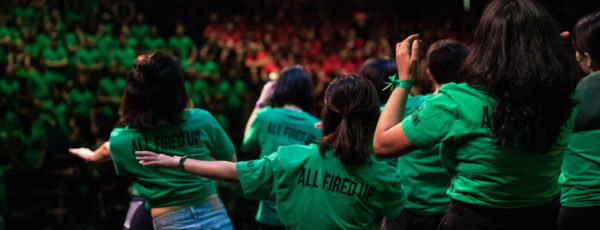 A group of MBA students in green shirts dancing at the cluster olympics. Teams include lions, tigers, bees, dragons.